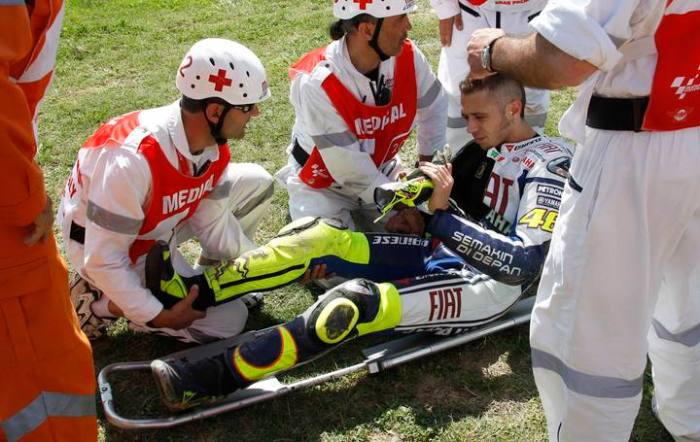 Yamaha MotoGP rider Rossi of Italy has his right leg checked by a doctor following a crash during the second free practice of the Italian motorcycling Grand Prix at the Mugello circuit